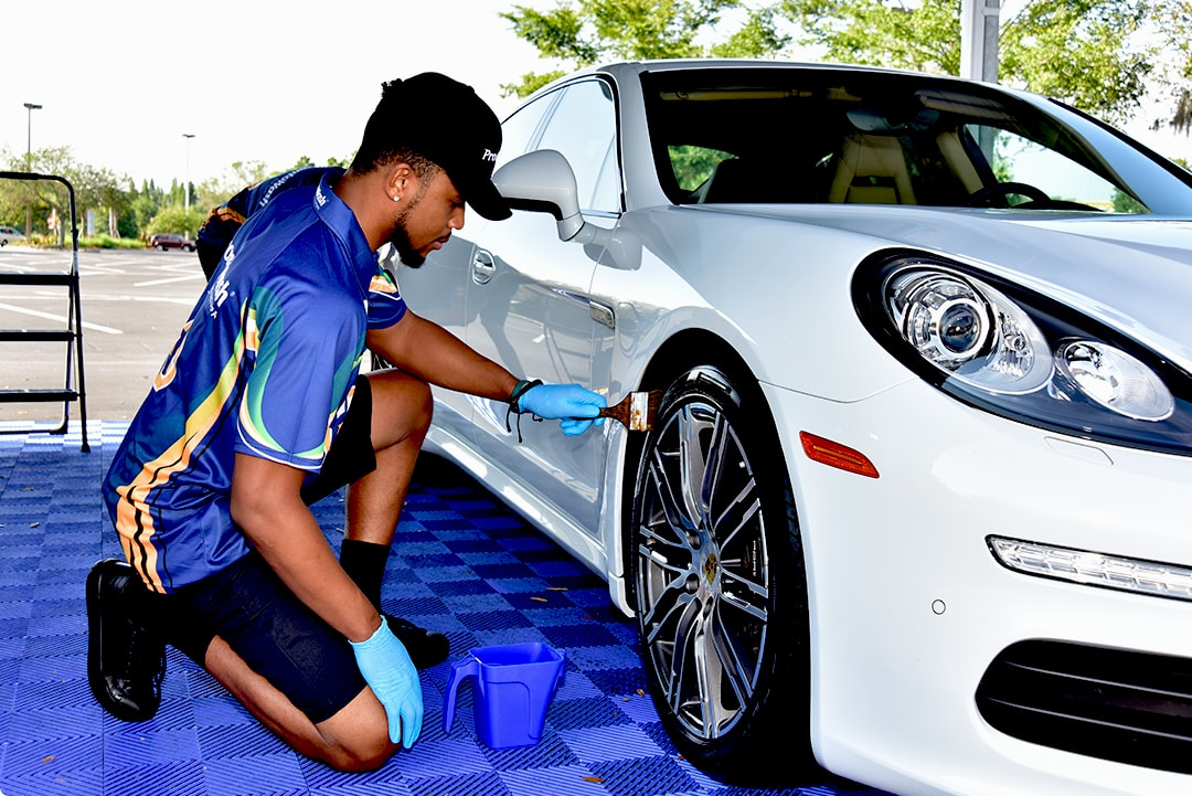 applying tire dressing at hand car wash